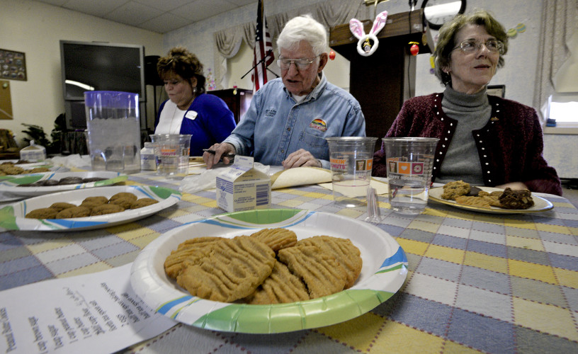 Vickie Harris-Williams, left, director of sales and marketing for Commonwealth Senior Living in Front Royal, Archie Fox, center, Warren County's Fork District supervisor, and Linda Glavis, right, Warren County's South River District supervisor and board chairman,  vote on their favorite cookies during the Shenandoah Area Agency on Aging's cookie baking contest held Thursday at the senior center in Front Royal. The group served as judges for the event. Rich Cooley/Daily