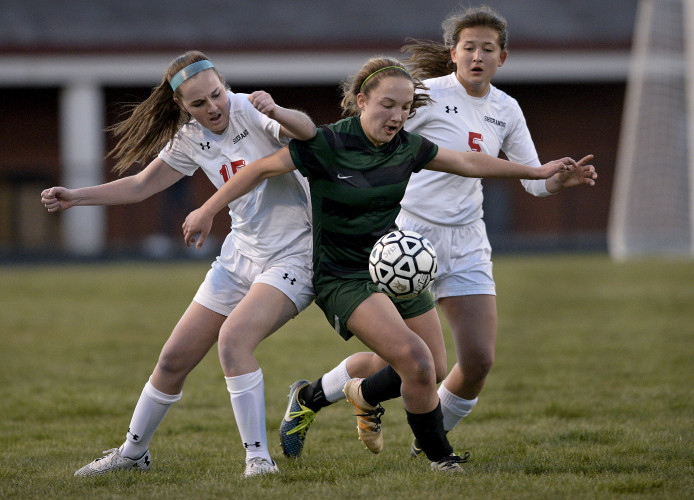 Shenandoah Valley Christian Academy's Sarah Max splits between Sherando's Catherine Price, left, and Lauren Heskett, right, during first half soccer Thursday night at Sherando High School. Rich Cooley/Daily