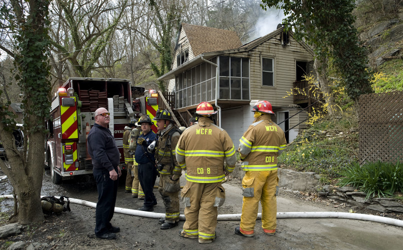 Warren County firefighters stand outside this home at 928 Bennys Beach Road that was destroyed by fire Friday afternoon. Rich Cooley/Daily