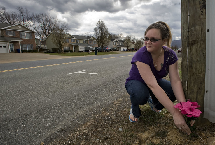 Jessica Lambert, 30, a Chester Gap volunteer firefighter, places flowers beside a utility pole outside the 100 block of Kerfoot Avenue on Monday  near the scene where police found Leah Marie Adams on Saturday night. Rich Cooley/Daily
