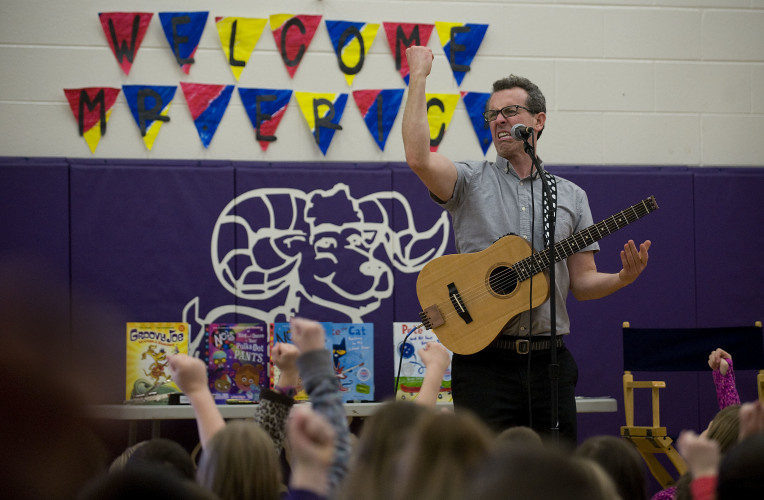 Eric Litwin, a children's author, tells a story with music to this group of  fourth and fifth grade students at Sandy Hook Elementary School on Tuesday. Litwin gave three presentations to the school and signed books that children purchased. Rich Cooley/Daily