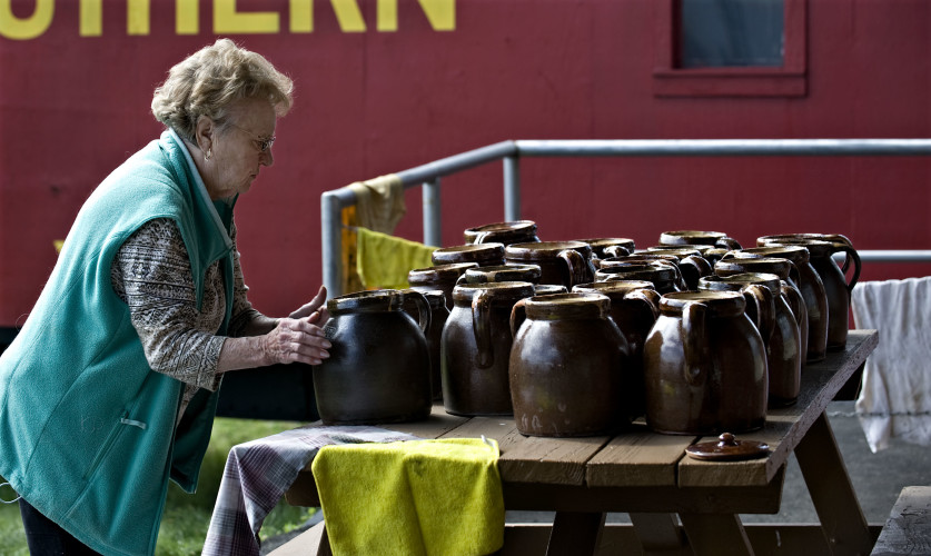Gloria Stickley, president of the Strasburg Museum, checks to see if a table of Eberly pots are dry after museum volunteers spent the morning cleaning over 200 pottery pots Wednesday morning. The museum's pottery room has been renovated with new floors and paint. The museum reopens in May.  Rich Cooley/Daily