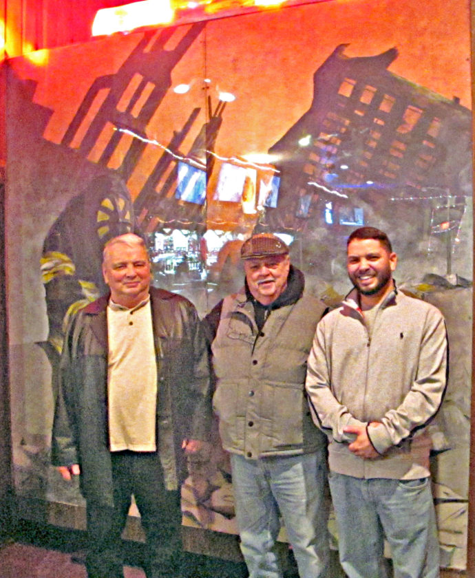 OBSERVER Photo by Rebecca Cuthbert Recently, Cody Stoyle's 9-11 tribute painting was installed permanently at the Exempts Club in Dunkirk. Before that, it hung in the lobby of Dunkirk High School for many years. Here, Stoyle (right) is pictured with his father Pat (left) and uncle Jim Stoyle (center) in front of his painting.