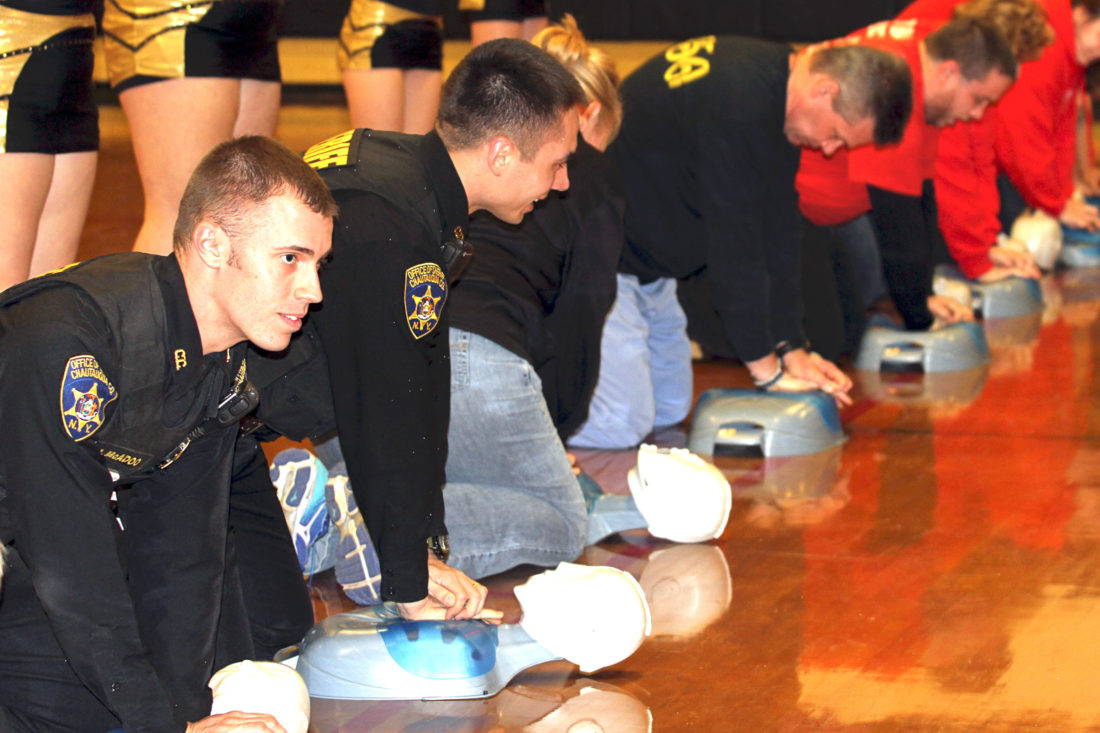 "OBSERVER Photo by Lisa Monacelli. Firefighters, Sheriff's deputies and others perform CPR on dummies to the song ""Stayin' Alive"" as part of a flash mob Thursday during halftime of the girls' varsity basketball game in Silver Creek. The game was in honor of Deputy Kevin Link, the late school resource officer for Silver Creek."