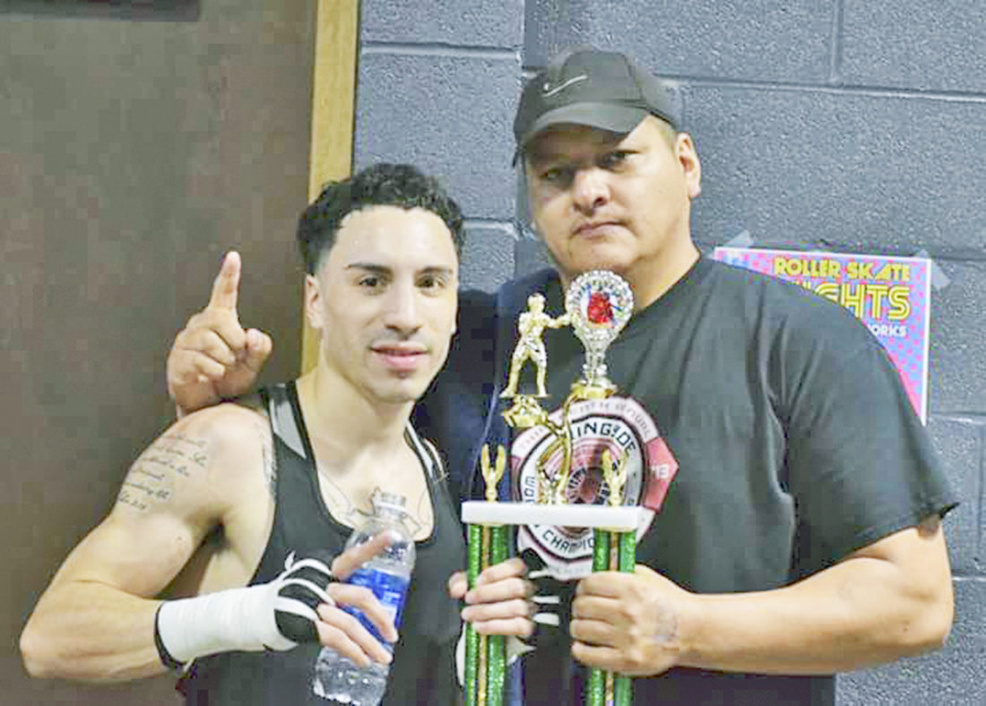 Submitted Photo Dunkirk native Elon Hernandez, left, is pictured with his first place trophy from the 123-pound Open division at the New York State Golden Gloves boxing championship on Saturday at the RiverWorks in Buffalo. Pictured at right is Hernandez's coach, Nate Jimerson.
