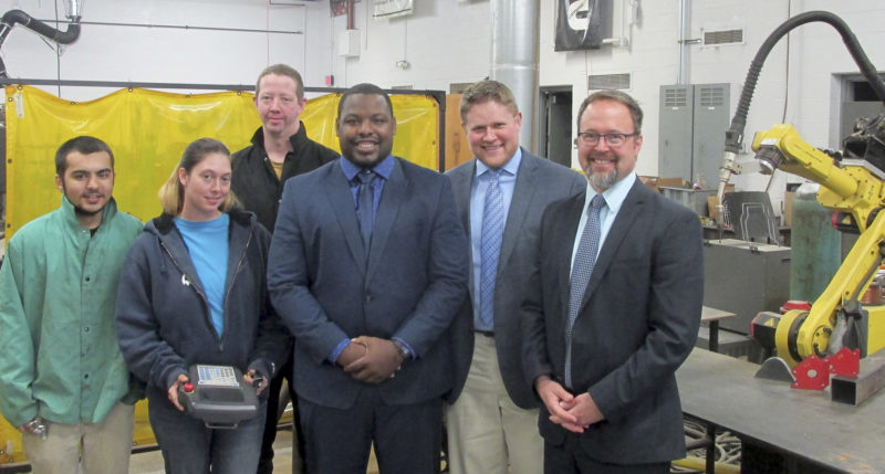 Submitted Photo JCC Manufacturing Technology Institute students Javon Hansraj, Cassandra Sanders and Patrick Sweeny show off robotic welding technology with Jehuu Caulcrick, new coordinator for Dream It Do It Chautauqua County and director of Industrial Services for the Manufacturers Association of the Southern Tier; Justin Hanft, director of the Chautauqua County Education Coalition; and Todd Tranum, executive director of the Manufacturers Association of the Southern Tier, President/CEO of Dream It Do It Western New York and president/CEO, Chautauqua County Chamber of Commerce.