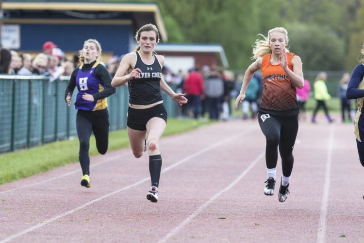 Photo by Tim Frank: Silver Creek's Emma Seiders competes in the 100-meter dash during Friday's Falconer Invite. The event was ended early due to thunder and lightning.