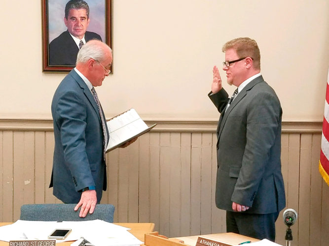 OBSERVER Photo by Greg Fox Newly appointed Fredonia Village Attorney Todd Thomas (right) recites his oath of office given to him by Village Administrator Richard St. George at Monday's village board meeting.