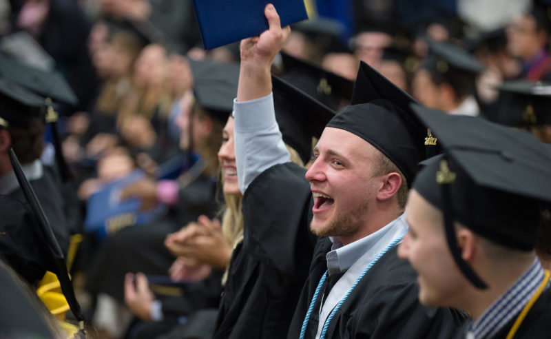 Photo Courtesy of State University of New York at Fredonia Luke Bartone, who majored in Marketing, joins his fellow classmates in signaling their enthusiasm to receive degrees at the State University of New York at Fredonia on Saturday. Two ceremonies were held at the Steele Hall Arena to accommodate the Class of 2017.