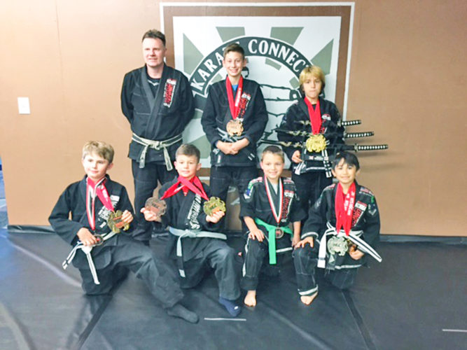 Submitted Photo Pictured Karate Connection competitors and their wins are as follows: In front, from left, Riley Mourer (first and fourth), Pauly Tabone (first and third), Josiah Ortiz (fourth) and Jaryel Vazquez (first and second). In back are promoter Norman Yonkers, Adam Sellari (third) and Milo Kinkela (first, first and Absolute Championship).