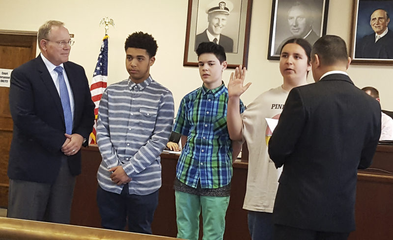 OBSERVER Photos by Nicole Gugino Top: Dunkirk Mayor Willie Rosas (right) swears in (from left) eighth-grade essay contest winners Cam'ron DeJesus, Anthony Morales and Justus Bowen as Supertintendent Dr. James Tracy looks on. Above: Dunkirk eighth graders Cam'ron DeJesus (left) and Anthony Morales (center) sit between First Ward Councilman Don Williams, Third Ward Councilman Adelino Gonzalez and Fourth Ward Councilwoman Stacy Szukala as they served as honorary council members at the recent Common Council meeting. Below: Dunkirk eighth grader Justus Bowen (center) sits between Dunkirk Mayor Willie Rosas and Attorney Sean Connolly as he served as honorary mayor at the recent Common Council meeting.