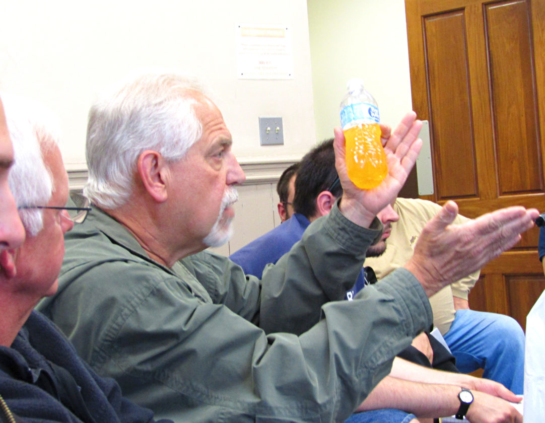 OBSERVER Photo by Greg Fox. Resident Paul Luce shows the Fredonia Village Board a bottle of yellowish-brownish water — the same water that comes out of his home's faucets.
