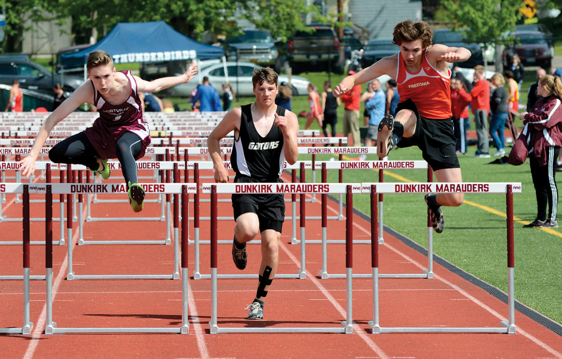 OBSERVER Photo by Justin Goetz Fredonia's Mike Meredith (right) clears the final hurdle in the 100 hurldes during Saturday's Chautauqua-Cattaraugus Athletic Association County Meet.