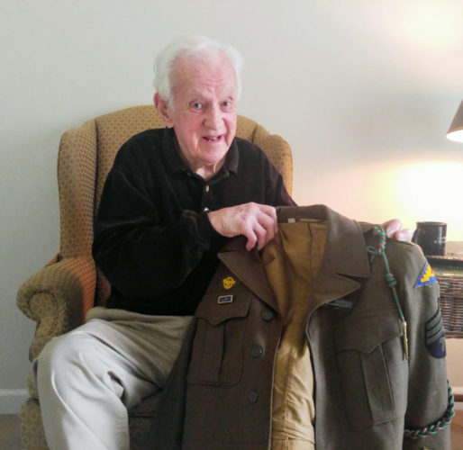 Submitted Photo John Carter Rowland holds up one of his uniforms he wore during WWII.