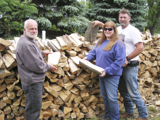 Submitted Photo At right, Gerry rodeo  head chef Bruce Gustafson (left) and rodeo chairman Tom Atwell and his wife Sharon finish stacking the wood which will be used to cook the barbecue beef for the dinners this Saturday at the Gerry Rodeo Grounds.