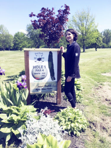 OBSERVER Photos by Marilyn Kurzawa Above: Myra Pinker stands at the sign designating the first hole at Rose Brook Golf Course.  At each hole there is a sign donated by an individual or a business. This one is dedicated to her parents, who were influential in her decision to buy the golf course. Right: Joey Miller uses a weed wacker to help keep Rose Brook looking good.