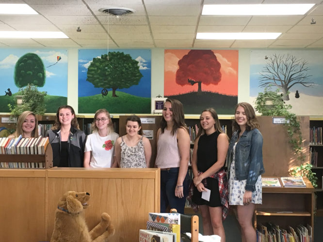 Submitted Photo Stop on by the Darwin R. Barker Library in Fredonia, where four new art pieces have been installed. Pictured are Fredonia high school students Brianna Cady, Alexis Cline, Alison Cortes, Paige Cronin, Brooke Erick, Lillyan Fuentes, Alisia Glasier and Hannah Koning, under the guidance of their Painting II instructor, Ms. Brandy Noody, not pictured. The students intend for these seasonal pieces to liven up the children's room at the library, as well as create a partnership between the library and its community.