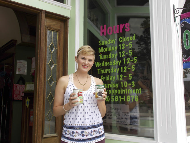 Submitted Photo: Brittany Mulkins of Little Sprouts Consignment Shop holds some of the food collected during the drive.