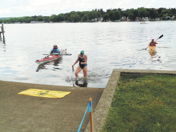 Photo by Jimmy McCarthy Great Lakes researcher and SUNY Fredonia professor Sherri Mason reaches the finish line of her 15.5-mile swim on Chautauqua Lake on Monday. Starting at Lakeside Park in Mayville, she finished at Lucille Ball Memorial Park in Celoron. The swim was timed at 10 hours and 37 minutes.