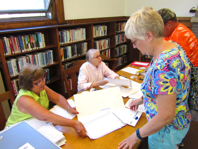 OBSERVER Photo by Greg Fox. Theresa Andrews (right) is given a ballot by elections inspector Cheryl Gawronski (left) during the Dunkirk Public Library budget vote and election on Tuesday. Also pictured is elections inspector Wilma Dopler.