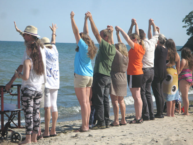OBSERVERPhotos by Amanda Dedie Top: People held hands to symbolize a unified front against the potential defunding of Great Lakes protection at Wright Park Beach.  Bottom: Almost 100 people lined the water's edge at Wright Park Beach on Monday morning.