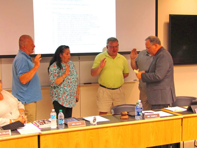 OBSERVER Photo by Greg Fox Dunkirk Superintendent of Schools Dr. James Tracy (right) administers the oath of office to members of the board of education during Thursday's meeting. Pictured reciting the oath, from left: Kenneth Kozlowski, Betsy Ramos, David Damico and Adam Reisenweber (back).