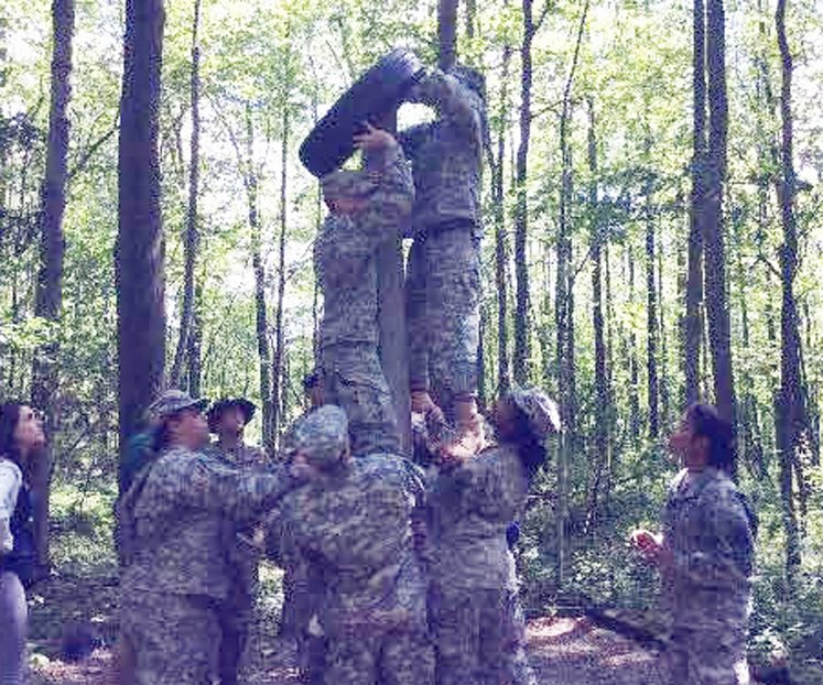 Submitted Photos Pictured at top is the high ropes exercise that builds confidence and ability in a safe environment. At left are cadets working together to place a tire above the pier as part of the Leader Reaction and Challenge Course.