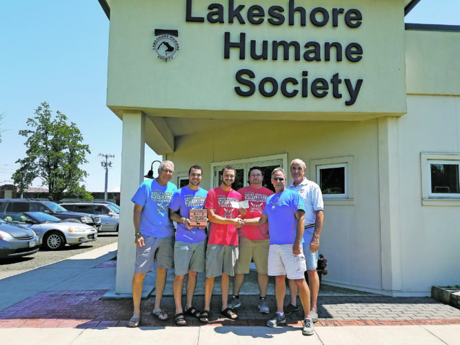 Submitted Photos Pictured above are Tom Tarnowski, Michael Tarnowski, Daniel Tarnowski, Michael Curtin, and representatives of Lakeshore Humane Society, Rock Vallone and Bob Ehrheart. Pictured at top is a group photo of all of the players who participated in the event.