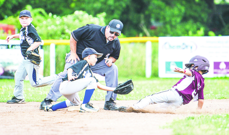 Dunkirk's Isiah Ruiz slides into second base under the watchful eye of the field umpire.
