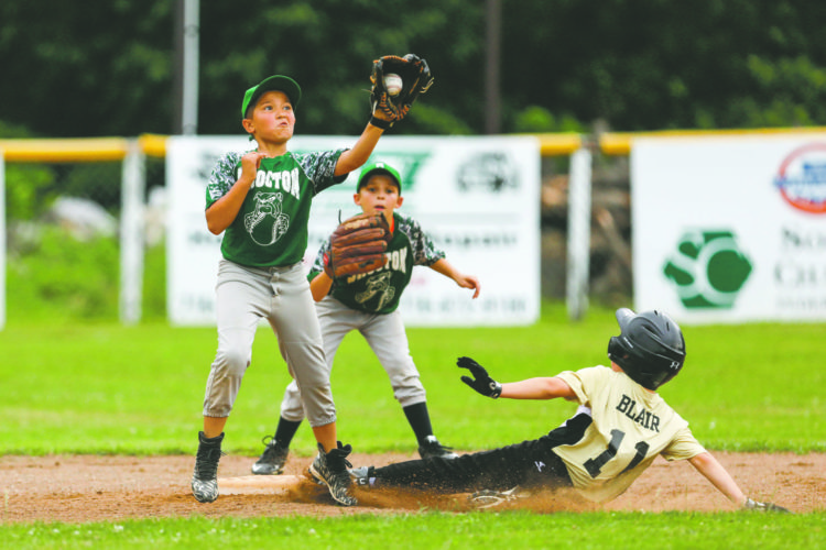 OBSERVER Photos by Joe Conti: Hanover's Dylan Blair (11) slides to the bag as Brocton's R. Santiago (11) fields the throw