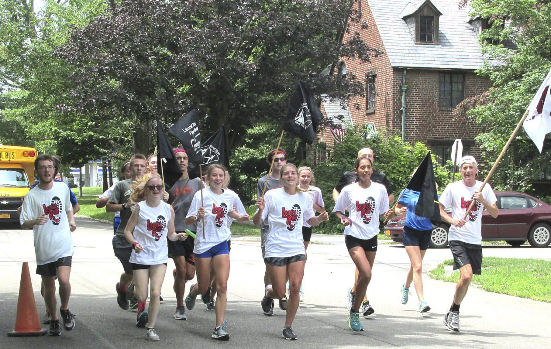 OBSERVER Photos by Damian Sebouhian.  Relay runners carry their Laurel Run flags across the finish line in Dunkirk. Michael Bird, publisher of the Post-Journal, is pictured in the far right.