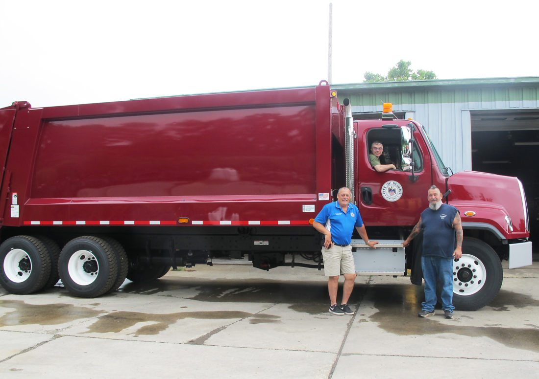 OBSERVER Photo by Nicole Gugino The city of Dunkirk's new garbage truck was delivered last week. The $165,000 truck is Dunkirk maroon with city of Dunkirk logos on the doors and a larger box to hold more trash. The truck was partially paid for with excess equipment funds. The crews will be trained on the new vehicle's features soon and it will be on the road next week. Pictured is Department of Public Works Director Bob Bankoski (left), Parks Department Supervisor Russ Tenamore and Mile Bailen (in truck).