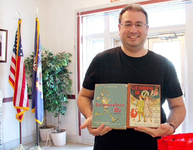 OBSERVER Photo by Tonja Dodd. Johnathan Courtis of Lakewood shows off two Oz books he purchased at the Westfield Antiques Show Sunday in Eason Hall.