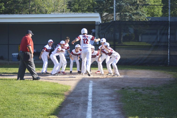 OBSERVER Photo by Jeremy Izzio. Bemus Point's Tucker Fenton touches home plate as his teammates cheer him on following a grand slam that blew the game open in the third inning.