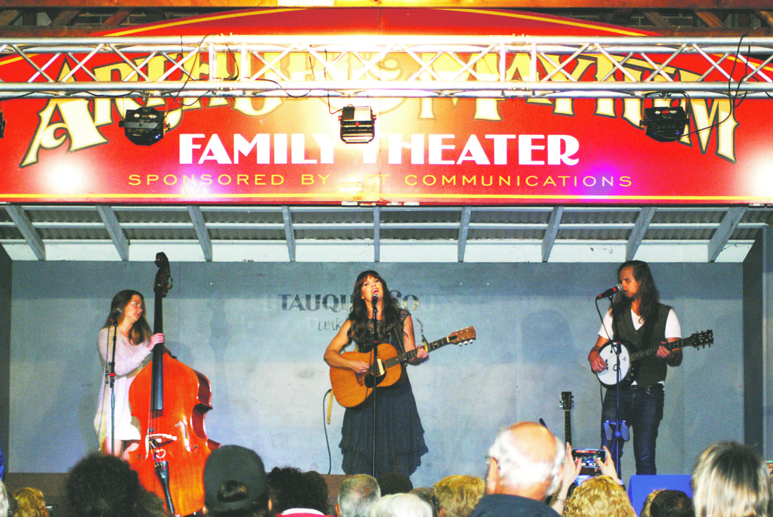 OBSERVER Photo by Jared Hill Nashville country singer and Fredonia native Ruthie Collins, center, sings Monday on opening night of the 136th annual Chautauqua County Fair.