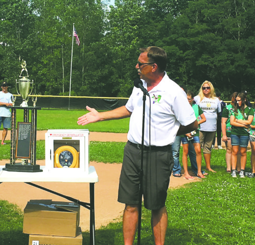 OBSERVER Photo by Andrew David Kuczkowski Hanover Little League Coordinator Keith VanVlack speaks after the Silver Creek Girl Scouts donated two automated external defibrillators, one for Silver Creek and other for Forestville, as the girl scouts are behind him.