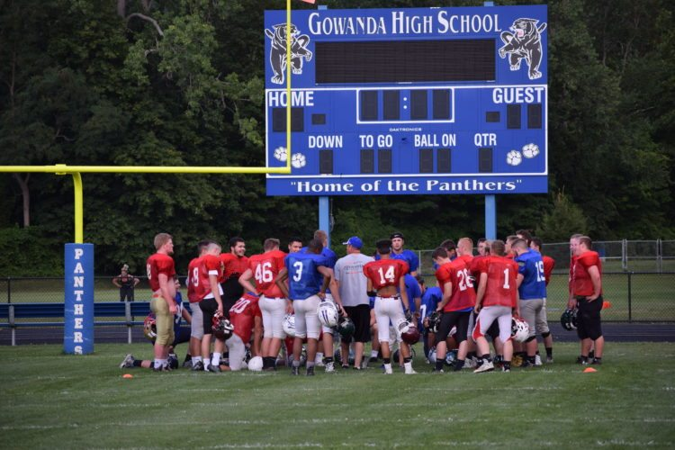 NY's Big 30 team huddles in an end zone as Gowanda and NY Big 30 coach Sean Gabel speaks to his conglomerate team.