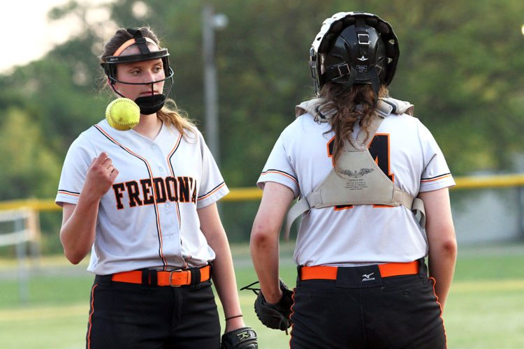 Hannah and Caitlyn Cybart converse in the circle during a high school varsity softball game.