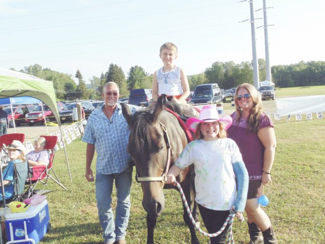 Photo by Jimmy McCarthy Horse rides at the Gerry Rodeo are being provided by MLW Stables out of Russell, Pa. Pictured from the left are Milton Wallace, owner, and volunteers Chase, Danielle and Samara.