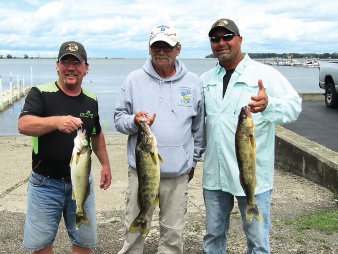 OBSERVERPhoto by Gene Pauszek From left, Darrin Pound, Tom Uhl and Rob Oram moved into the top spot for total weight with a three-walleye total of 14.09 pounds caught on Friday evening and Saturday morning out of Barcelona.