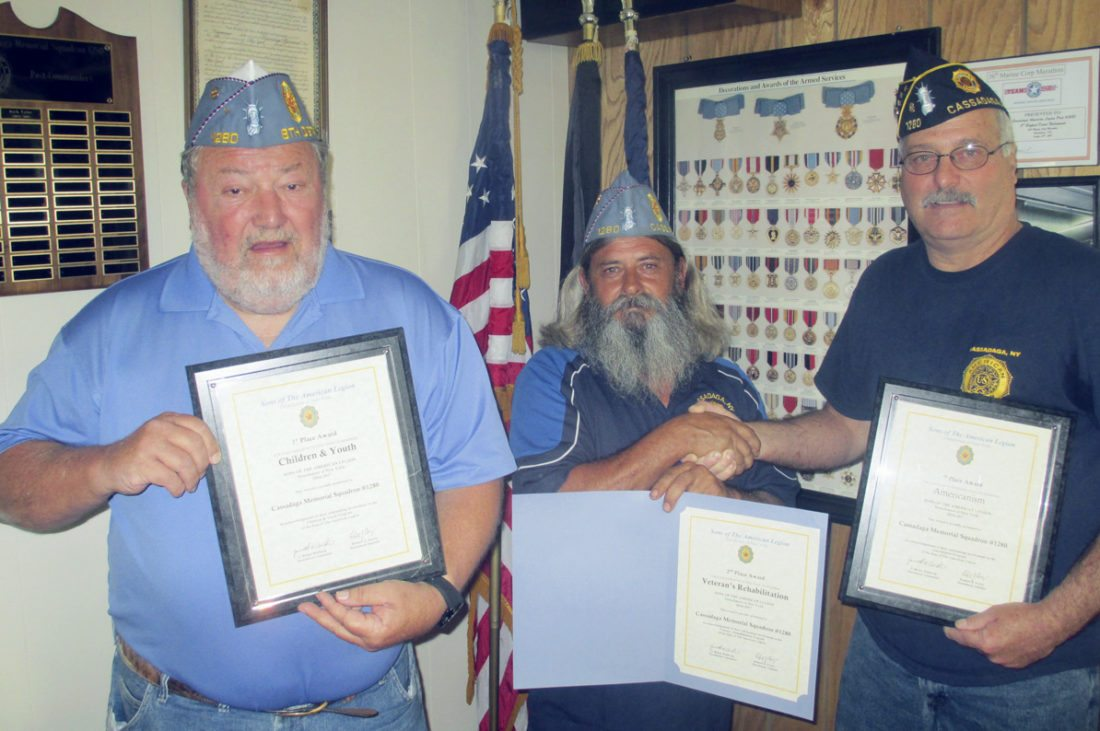 "Submitted Photo: The Cassadaga Legion Memorial Post 1280 Sons of American Legion Squadron was honored with awards. The awards were presented at the recent American Legion, Department of New York convention. The Sons received a first place award for their Americanism program, a first place award for Children and Youth program and a second place award for Veteran's Rehabilitation program. The awards were presented to the Sons of the American Legion Squadron 1280 commander Diman Smith at the Department convention in Syracuse. Pictured are, left to right: Robert Ellis, Squadron adjutant; Smith, Squadron commander; and Charles ""Rusty"" Jones, Legion Post 1280 commander, congratulating the Sons' commander."