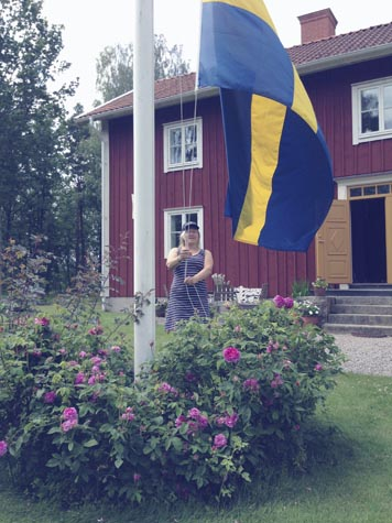 Pia Dahl raises the Swedish flag at her home in Vaxjo, Sweden.