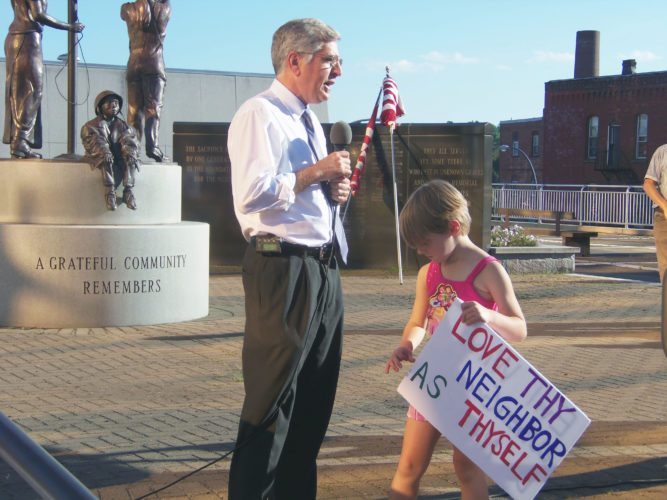 "Photo by Katrina Fuller A young girl stands near Jamestown Mayor Sam Teresi as he discusses the events of Charlottesville, Va. during the ""Not In Our Town: Demonstration For Love and Tolerance"" in Tracy Plaza on Wednesday night."