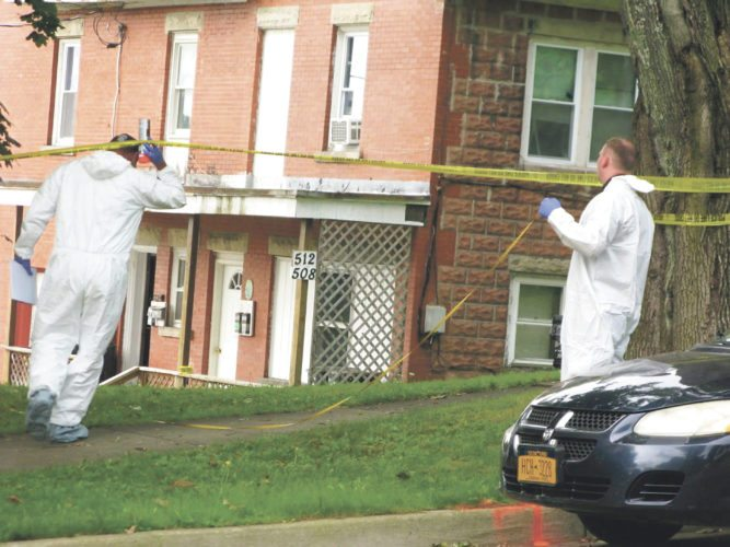 "Photo by Eric Tichy A member of the Chautauqua County Forensic Investigation Team at the scene Saturday of a ""suspicious death"" on East Sixth Street in Jamestown."