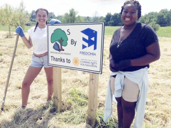 Submitted Photo SUNY Fredonia students Oriana Garcia (left) and Takara Alleyne take a break from their tree-nurturing activities at Greystone Nature Preserve.