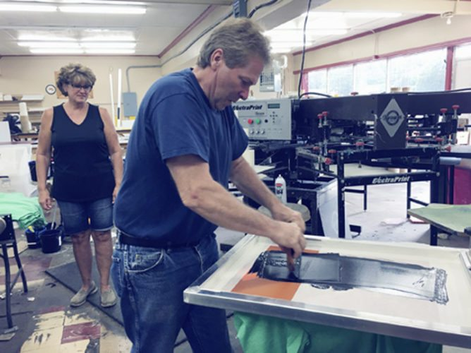 OBSERVER Photos by Marilyn Kurzawa Above: John Hilliker squeezing the ink through a silk screen at Hae Jude Custom Signs. Far left: Laurie Bifaro standing behind the desk at A Cut Above the Rest. Left: Judy Hilliker holding a large decal printed on this machine.