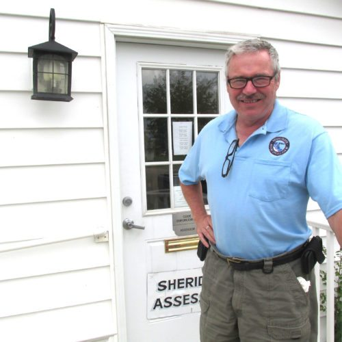 Photo by Damian Sebouhian: Jim Crowell, code enforcement officer for Sheridan, stands in front of his office near town hall.