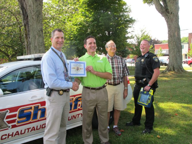 Photo by Eric Tichy: Chautauqua County Sheriff's deputy Michael Seeley, far right, laughs in August 2013 after being recognized for helping to save the life of a Pennsylvania man, second from right, who suffered a heart attack in Hartfield. Seeley was diagnosed with acute myeloid leukemia after a routine physical showed abnormal white blood cells.
