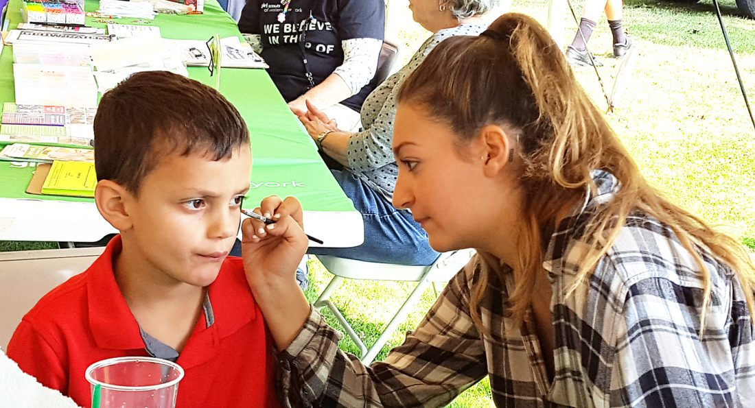 OBSERVER Photo by Nicole Gugino United Way of Northern Chautauqua County intern Nicole Snyder (right) paints a flame on Alan Kapple's face Sunday during Picnic at the Point.
