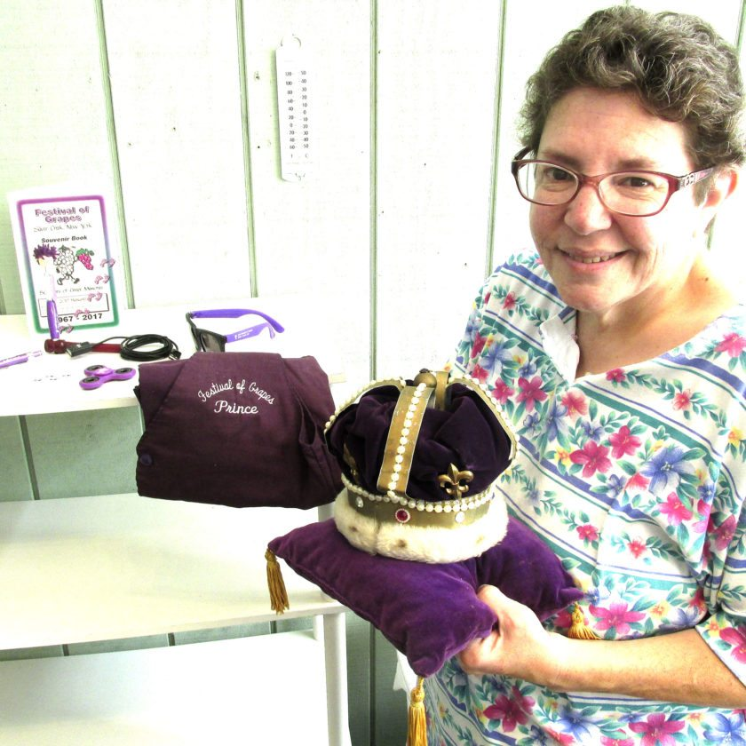 OBSERVER Photo by Damian Sebouhian Chairwoman of Festival of Grapes Headquarters Lisa Romano holds the pillow and crown used during the very first Festival of Grapes held in 1967. Behind Romano are samplings of souvenirs for sale during the festival.